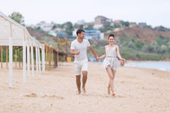 Barefoot couple on sand seashore in cloudy day Royalty Free Stock Image