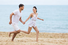 Barefoot couple on sand seashore in cloudy day Royalty Free Stock Photos