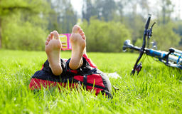 Barefoot cyclist on a halt reads lying in fresh green grass Stock Image