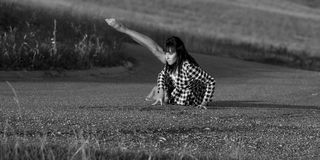 Barefoot dancer lifting up a leg on a country road. Stock Images