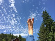 Barefoot feeling free in the sky. Yoga foot rising up in the blue sky Royalty Free Stock Images