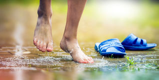 Barefoot the feet of the boy and ankle in a mud puddle. Royalty Free Stock Photography