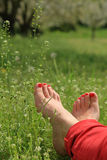 Barefoot female feet on green field Stock Photos