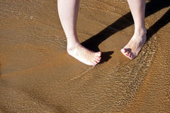 Barefoot female feet  in surf on. Girl feet in sea water wave Royalty Free Stock Photos