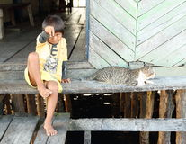 Barefoot fisherman´s kid with cat Stock Image