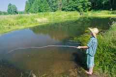 Barefoot fishing boy standing in transparent Stock Image