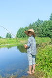 Barefoot fishing boy standing in transparent yellowish waterbody Royalty Free Stock Images