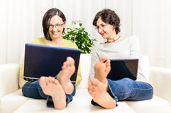 Barefoot funny happy women chat browsing home laptop Stock Image