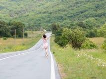 Barefoot  girl on the asphalt road Stock Images