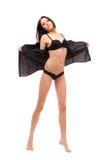 Barefoot girl in black lingerie Stock Images