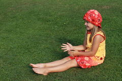 Barefoot girl catching something. Barefoot little girl in red and yellow dress sitting and catching something royalty free stock image