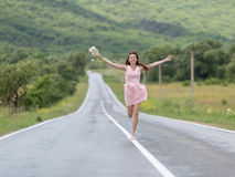 Barefoot girl with chamomile bouquet running along road Stock Images