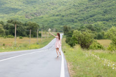 Barefoot girl with chamomile bouquet running along road after ra Stock Photo