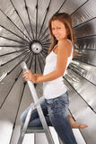 Barefoot girl climbed on ladder near umbrella Royalty Free Stock Photos