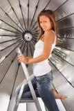 Barefoot girl climbed on ladder near umbrella Royalty Free Stock Photos