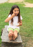 Barefoot girl eating Royalty Free Stock Images