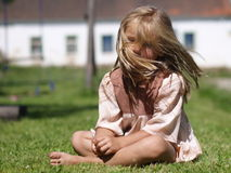 Barefoot girl on grass. Little barefoot girl sitting on grass royalty free stock photography