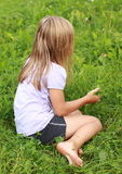 Barefoot girl on grass. Barefoot little girl in soft blue t-shirt and black shorts sitting on grass Stock Image