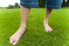 Barefoot girl in grass Stock Images