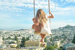 Barefoot girl hugging teddy bear on vintage swings high above ci. Barefoot girl in white dress hugging teddy bear, flying on vintage swings high above city, view Stock Photo