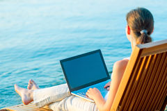 Barefoot girl with a laptop on the beach Stock Images