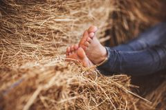 Barefoot girl legs on haystack Stock Photo