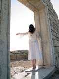 Barefoot Girl Looking Straight Ruins. Barefoot girl on tiptoe looks straight holding ancient wall Stock Photos