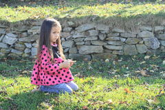 Barefoot girl on meadow. Little barefooted kid - sad girl with long brown hair in pink t-shirt with black dots and blue jeans kneeing on meadow in front of stone Stock Photos