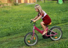 Barefoot girl riding a bike. Little barefoot girl in red dress riding a bicycle stock photos