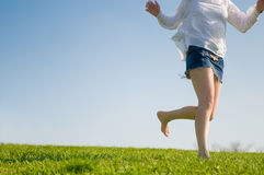 Barefoot girl runs on a green lawn Stock Photos