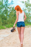Barefoot girl in shorts and a t-shirt outdoors Stock Images
