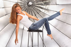 Barefoot girl sits on chair near umbrella Royalty Free Stock Image