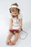 Barefoot girl sitting in big headphones Stock Photo