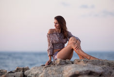 Barefoot girl sitting on rock Royalty Free Stock Image