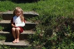 Barefoot girl sitting on the stairs. Barefoot girl in red dress with broken hand sitting on old stairs royalty free stock image