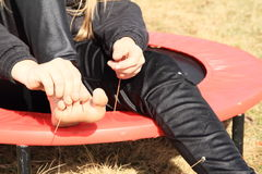 Barefoot girl sitting on trampoline. Blond girl - smiling barefoot kid in black clothes sitting on black and red kids´ small trampoline and playing with her Royalty Free Stock Photos