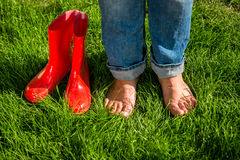 Barefoot girl standing next red garden gumboots on grass Royalty Free Stock Photography