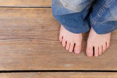 Barefoot girl standing on wooden floor. Close up barefoot girl standing on wooden floor - from above Royalty Free Stock Images
