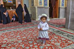 Barefoot girl stands at entrance to mosque in beach hat. Stock Image