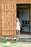 Barefoot girl in a summer sundress stands in the doorway of the shed royalty free stock image