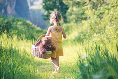 Barefoot girl walking with picnic basket in the wood Stock Photo