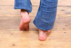 Barefoot girl walking on wooden floor Stock Photo