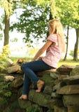 Barefoot girl on wall Stock Photography