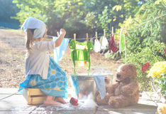 Barefoot girl washing her toys clothes near washtub Stock Images