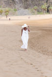 Barefoot girl in white hat and dress walking on a beach Royalty Free Stock Photo