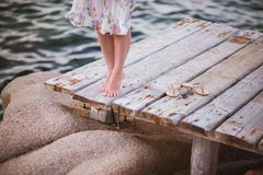 Barefoot girl on wooden bridge above water Stock Image