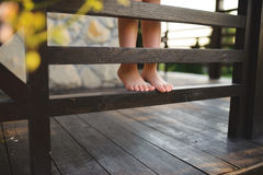 Barefoot Girl on Wooden Fence of Porch. Barefoot girl standing on wooden fence of porch royalty free stock photos