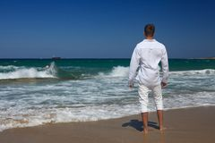 Barefoot guy standing near the sea, horizontal Royalty Free Stock Images