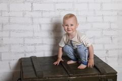 Barefoot handsome little boy smiles and squats. On wooden box in room Stock Images