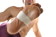 Barefoot kick. Closeup of bottom of man's foot with middle of foot wrapped with sports tape as he does martial arts kick on white background stock photos